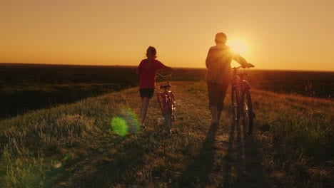 An-Elderly-Lady-Walks-With-Her-Granddaughter-Bicycles-At-Sunset-2