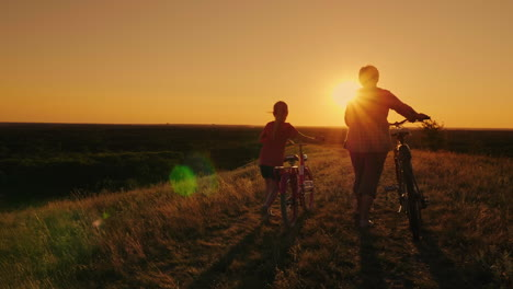 Back-View:-An-Elderly-Lady-Walks-With-Her-Granddaughter-Bicycles-At-Sunset