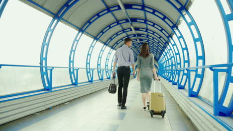 A-Man-And-A-Woman-Go-With-Luggage-At-The-Terminal-Of-The-Station-Or-Airport