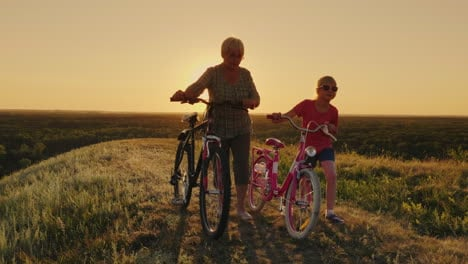 An-Elderly-Lady-Walks-With-Her-Granddaughter-Bicycles-At-Sunset-3