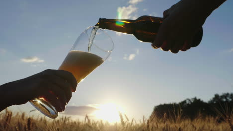 Pour-The-Beer-In-A-Glass-Against-A-Blurred-Background-From-The-Barley-Field