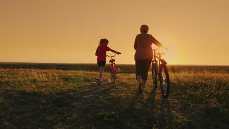 Back-View:-An-Elderly-Lady-Walks-With-Her-Granddaughter-Bicycles-At-Sunset-1
