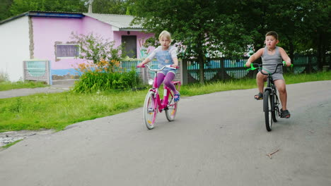 Two-Carefree-Children---A-Girl-And-A-Boy-Ride-Bicycles-On-The-Street-1